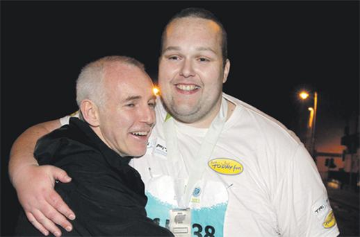Ray D'Arcy embraces Gary Kirwan at the finish line after his 10-hour marathon