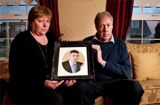 Anne and John Higgins with a photo of their son David