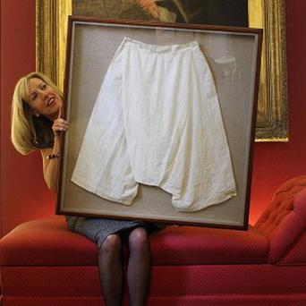 Staff member Kate Bain holds a pair of silk bloomers belonging to Queen Victoria, which fetched 9,375 pounds at Lyon & Turnbull auction house