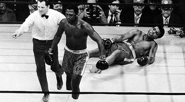 Joe Frazier is led to a neutral corner after knocking down Muhammad Ali in the 15th round of their 1971 title bout