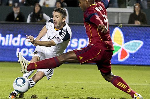 Robbie Keane shoots past Real Salt Lake defender Jamison Olave to score