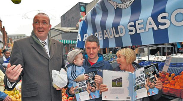 Pat Gilroy on Dublin's Moore Street yesterday with street trader Rosie Farrell, her grandson Lennon Owens (1) and his dad Ross Owens, to promote the official Dublin photography book, 'A Rare Auld Season'