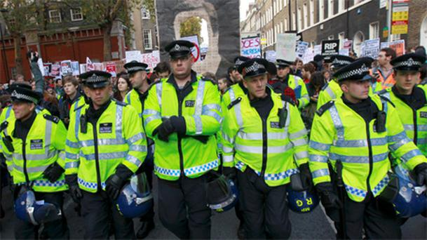 Police officers walk ahead of student protestors in central London