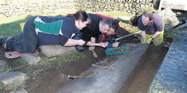 Archaeologists view bone fragments found at a dig in Newtown Jerpoint