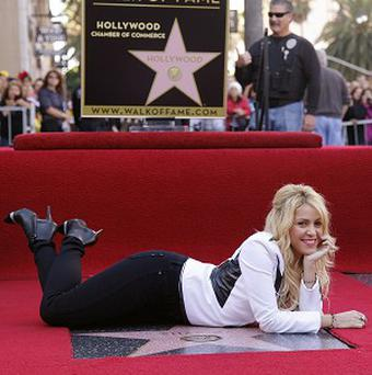 Shakira poses as she is honoured with a star on the Hollywood Walk of Fame