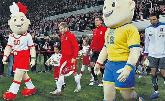 Euro 2012 mascots Slavek and Slavko walk out with players during a football friendly between Italy and Poland at the Wroclaw Stadium, one of the tourname