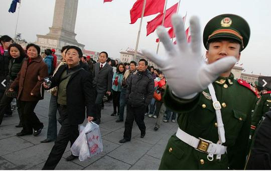A police officer tries to prevent photos being taken in Beijing's Tiananmen Square. Photo: AP