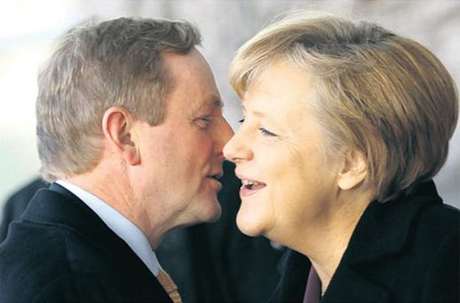 Taoiseach Enda Kenny gives German chancellor Angela Merkel a kiss on the cheek when the two leaders held a meeting in Berlin yesterday. Photo: Reuters