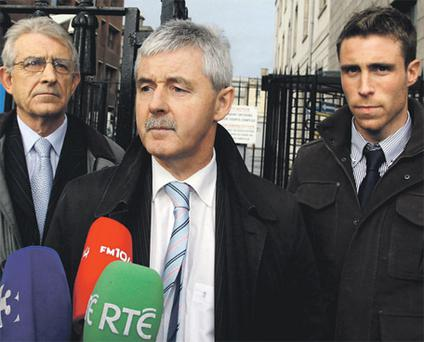 Wayne O'Donoghue and his father Ray listen to solicitor Frank Buttimer make a statement outside the court yesterday