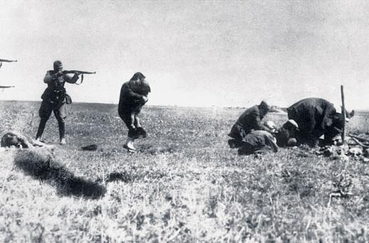 A German soldier points his weapon at a woman holding a child in the Ukraine while three or four people crouch down during World War Two.