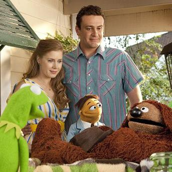 Amy Adams and Jason Segel are shown with muppet characters in a scene from The Muppets (AP/Disney)