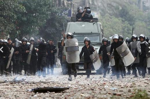 Egyptian riot police are seen on the move during clashes with protesters in Tahrir Square. Photo: AP
