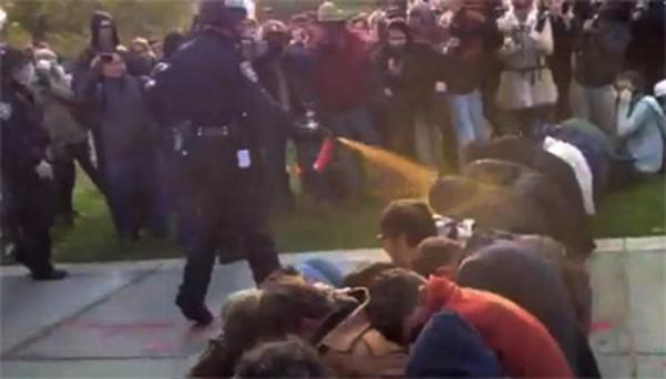A police officer uses pepper spray as he walks down a line of Occupy demonstrators sitting on the ground at the University of California
