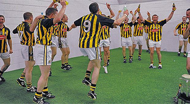 With the Liam MacCarthy Cup secured and placed in the corner after victory against Tipperary, Kilkenny's players celebrate re-capturing the All-Ireland SHC title