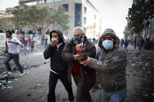An injured protestor is led away during clashes with police near Tahrir Square on November 23. Photo: Getty Images