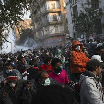 Protesters run from tear gas in Cairo (AP)