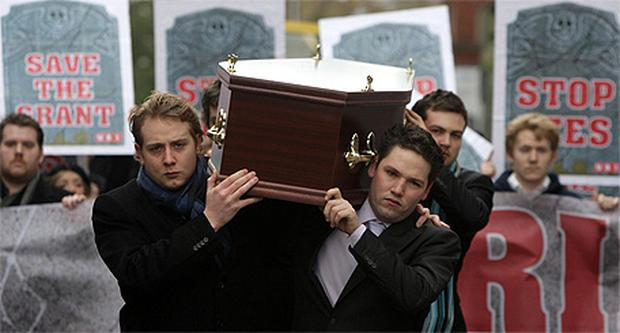 Colm Murphy and Gary Redmond, members of the Union of Students in Ireland (USI) carry a coffin to the gates of Leinster House in Dublin as students today mourned the 'death of education'