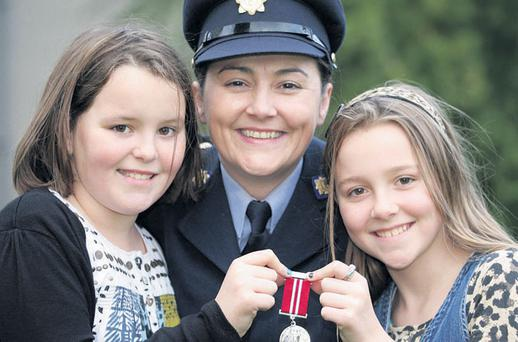 Garda Linda O'Donnell with her silver medal for bravery and her twin daughters, Eve and Mary (11) at Farmleigh House yesterday