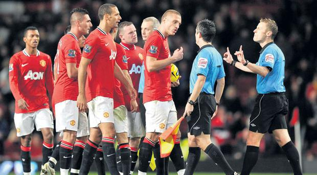 Manchester United players approach referee Michael Jones after the final whistle at Old Trafford to complain about the penalty awarded to Newcastle. Photo: Martin Rickett