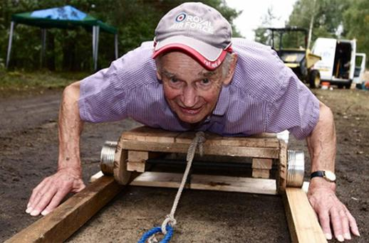 Veteran Frank Stone demonstrating a trolley at the entrance to a recreation of the famous 'Harry' escape tunnel. Photo: PA