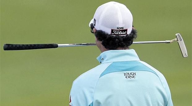 Rory McIlroy holds his putter in his mouth on the 18th green after enduring a frustrating final round at the World Cup alongside playing partner Graeme McDowell