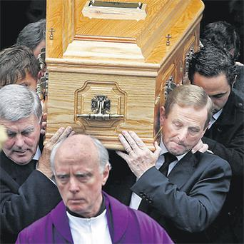 Taoiseach Enda Kenny carries his mother's coffin after her funeral Mass yesterday