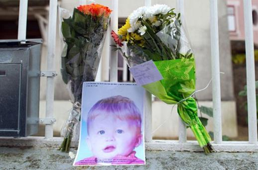 Flowers and a picture of three-year-old child Bastien at the entrance of the child's parents house on in Meaux, near Paris. Photo: Getty Images