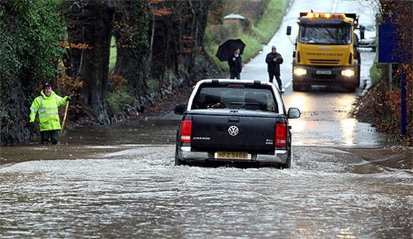 A 4x4 vehicle drives through the flooded Liminary Road in Kells, Co Antrim