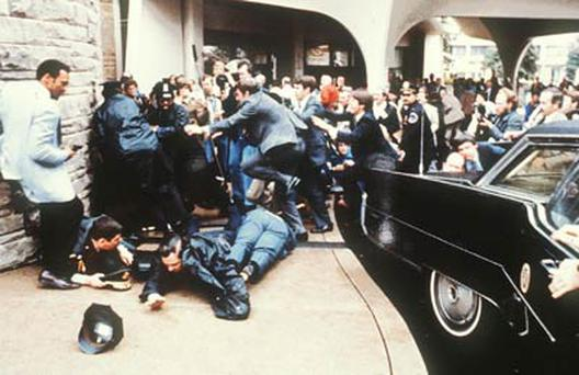 Police and Secret Service agents dive to protect President Ronald Reagan amid a panicked crowd during the assassination attempt by John Hinkley Jr