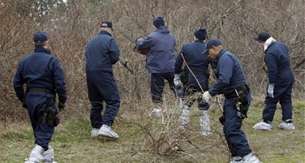 Emergency personnel use a chainsaw to search through the brush for human remains near Jones Beach in Wantagh. Photo: AP