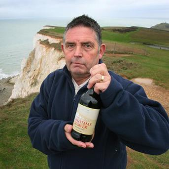 Keith Lane, 61, whose wife Maggie died at the cliffs at Beachy Head, holds a bottle of Beachy Head Christmas Jumper beer