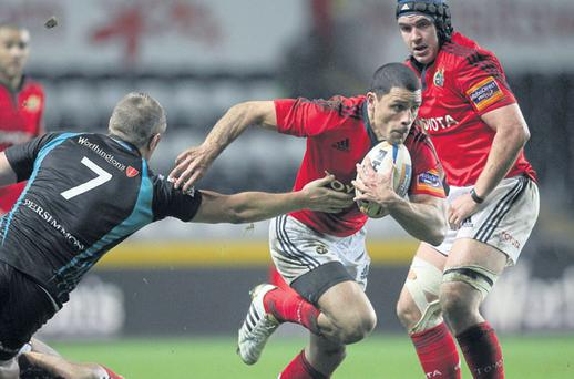 Munster's Doug Howlett evades the tackle of James King of Ospreys during their clash at the Liberty Stadium.