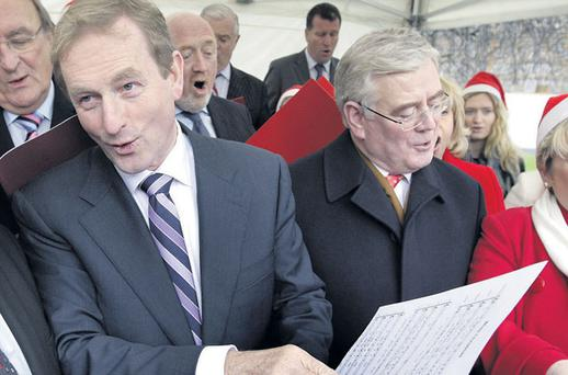 THE SONG REMAINS THE SAME: Enda Kenny, carol singing with the Oireachtas Choir as the Leinster House Christmas lights were switched on, is accused of 'continuing the reactionary programme of the old order'
