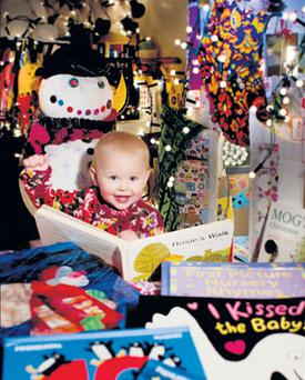 FIRST GLANCE: Eighteen-month-old Isobel Conachy with her pick of the Christmas books. With such a wonderful supply of new children's titles around this year, along with so many old favourites, we're spoilt for choice. Photo: David Conachy