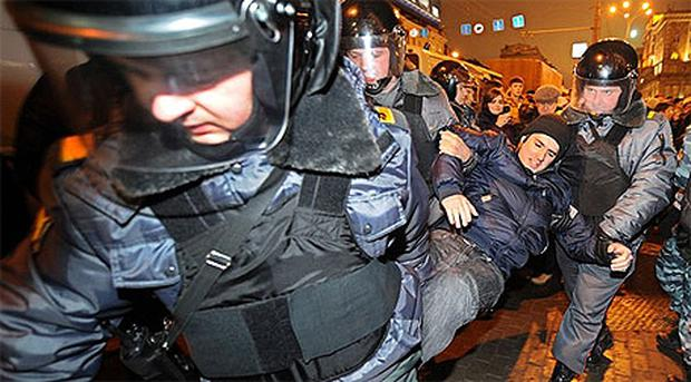 Riot police carry away an opposition activist during an unauthorized rally in Triumfalnaya Square in central Moscow
