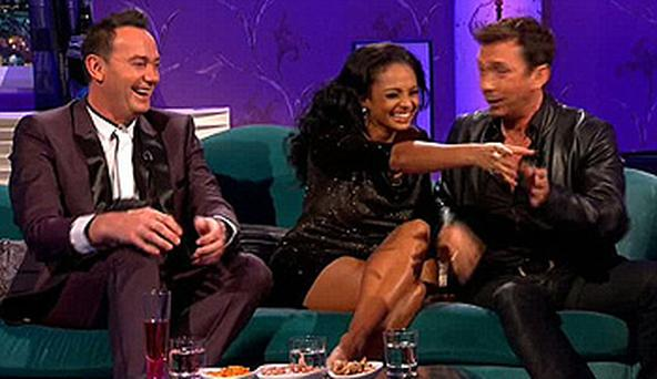 Alesha Dixon reaches for a bottle of wine from chat show host Alan Carr
