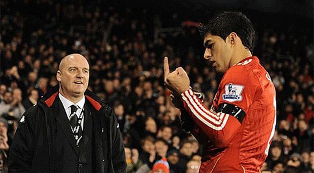Liverpool's Luis Suarez makes a one-fingered gesture towards the crowd at Craven Cottage