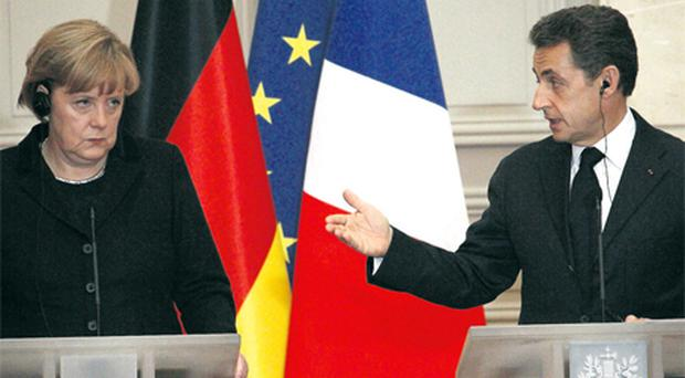Franco/German relations eventually thaw as President Nicolas Sarkozy and Chancellor Angela Merkel shake on it at a joint press conference after crisis talks at the Elysee Palace, Paris, yesterday. Photo: Getty Images