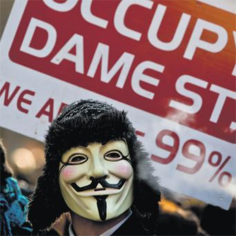 A protester from the 'Occupy Dame Street' movement protests outside Dail Eireann yesterday