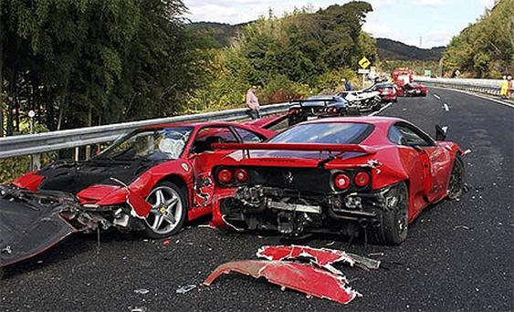 Police officers inspect the damaged Ferrari sports cars on the Chugoku highway in Shimonoseki, Yamaguchi prefecture, western Japan following a 14-vehicle pile up