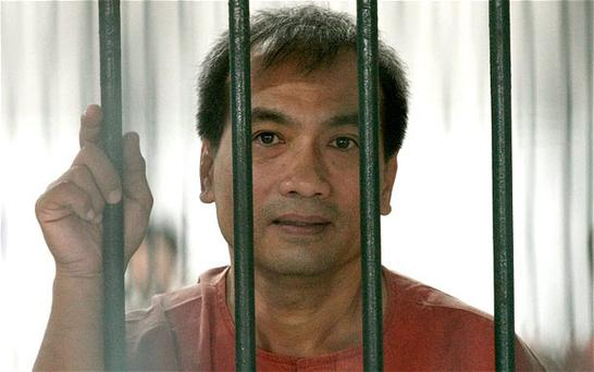A Thai-born US citizen Joe Gordon looks on from inside a cell at the criminal court in Bangkok.