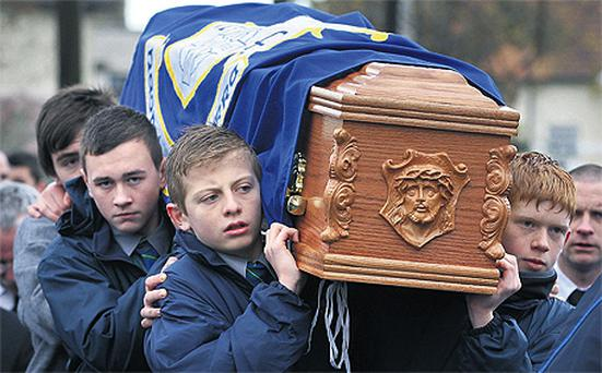 Schoolboys from Gaelscoil Colaiste Mhuire carry Conor Hickey's coffin to Christ the King Church, Cabra, Dublin yesterday