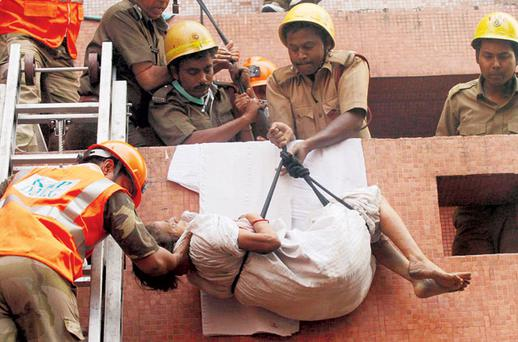 Firefighters rescuing a patient from the AMRI hospital, Calcutta, India, yesterday, after it caught fire. Photo: REUTERS
