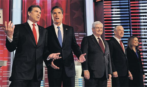 Texas governor Rick Perry, left, talks with former Massachusetts governor Mitt Romney, while former house speaker Newt Gingrich, congressman Ron Paul and congresswoman Michele Bachmann wait for the start of the debate on the campus of Drake University, Iowa, at the weekend