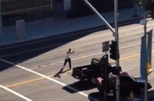 Amateur video shows a lone gunman shooting at a passing vehicle in Hollywood in footage filmed before he was shot dead by an off-duty policeman. Photo: YouTube