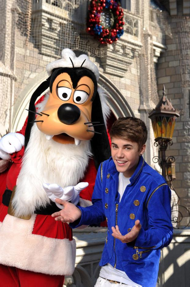 LAKE BUENA VISTA, FL - DECEMBER 03: In this handout image provided by Disney Parks, Justin Bieber poses with Santa Goofy during a break while taping a performance segment for the