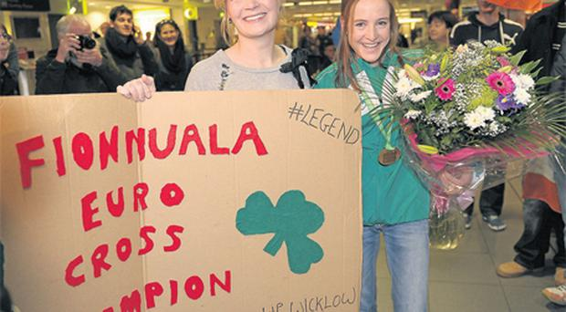 Fionnuala Britton is welcomed home at Dublin Airport last night by Kilcoole AC team-mate Deirdre McDermott