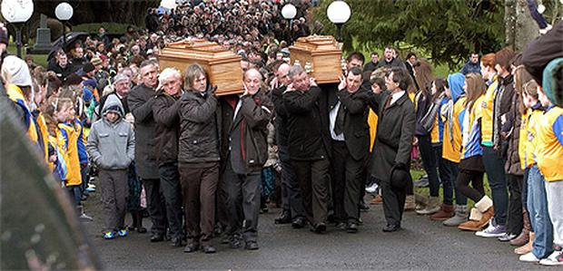 The coffins of Sandra Herbert and her daughter Rachel are carried from Christ the King Church in Knockmore, Mayo, yesterday followed by a large crowd of mourners