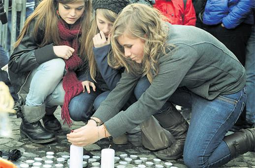 Women light candles at the site of a gun and grenade attack in central Liege yesterday