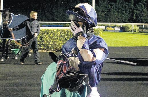 Kirsty Milczarek, who has received a two-year ban over corruption breaches, hides her face from the camera as she leaves the paddock at Kempton last night